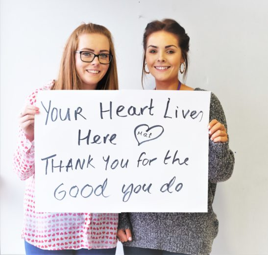 "Your Heart lives here aMQI Project works Jenny and Amy holding sign reading "" Thank you for the Good you do"""